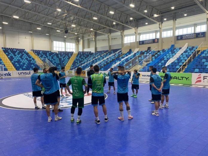 #Pracegover Foto: na imagem há jogadores de futsal uma quadra e arquibancada