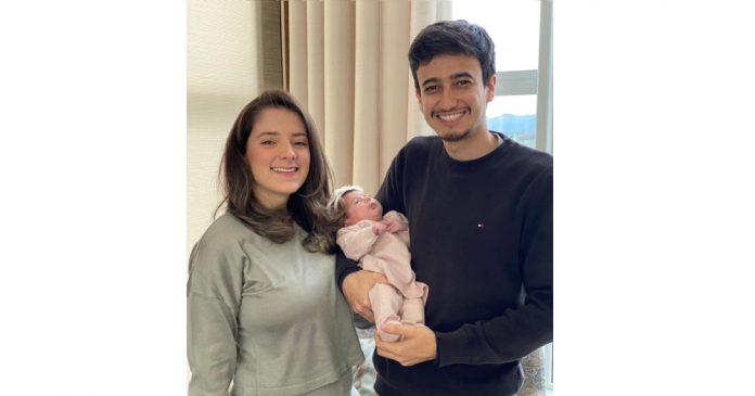 #Pracegover Na foto, casal segurando um bebê