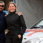 #Pracegover Na foto, homem e mulher estão ao lado de um carro de corrida