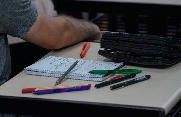 #Prcegover Foto: na imagem há canetas, folhas, um braço e uma mesa