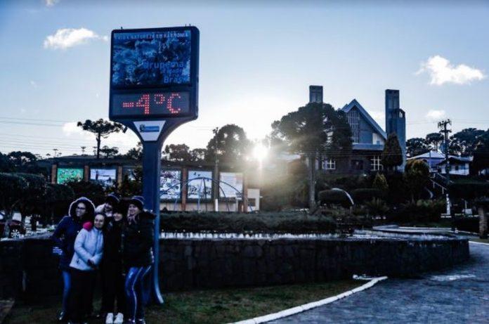 #Pracegover Foto: na imagem há pessoas, casa, árvores