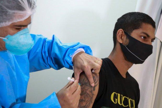 #Pracegover Foto: na imagem há duas pessoas, uma aplicando a vacina e outra recebendo