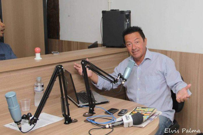 #Pracegover Foto: na imagem há um homem, microfone, mesa, jornais e celulares