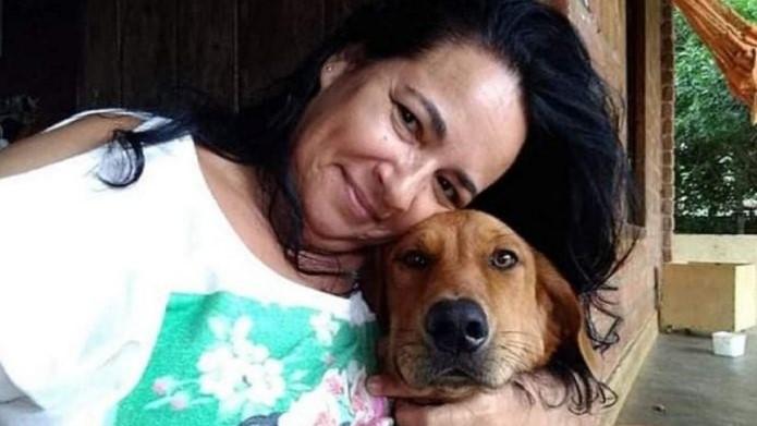 #Pracegover Na foto, mulher está abraçada com um cão