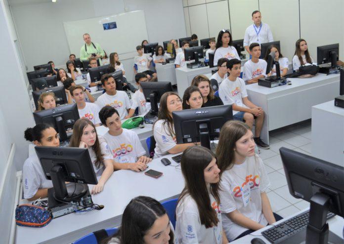 #Pracegover foto: na imagem há pessoas, computadores, mesas e cadeiras