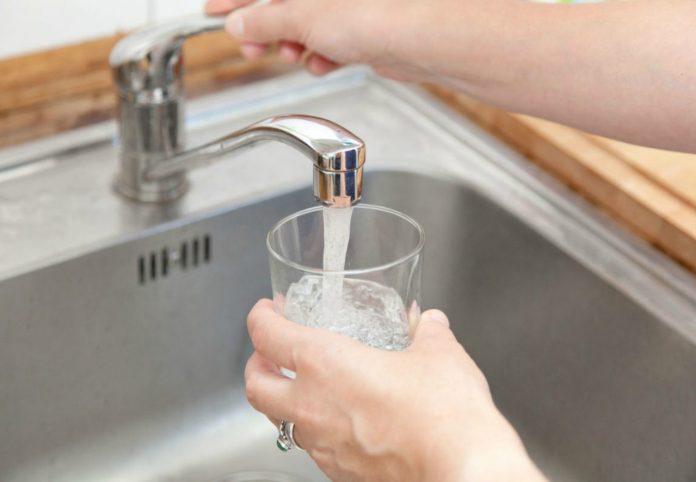 #Pracegover foto: na imagem há uma torneira, mãos e braço, água e uma pia