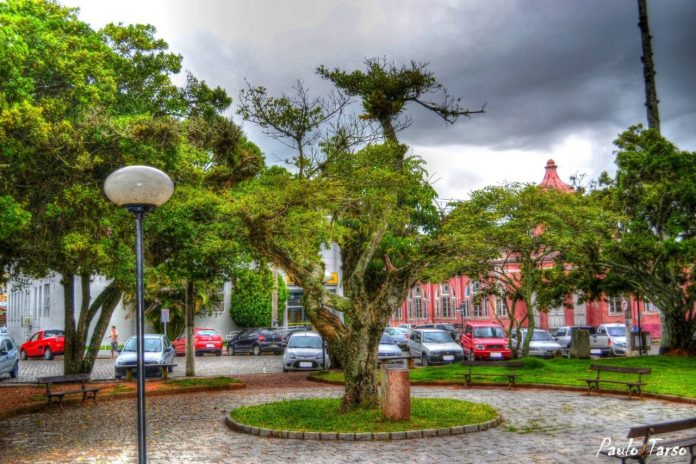 #Pracegover Foto: na imagem há uma praça, árvores e construções