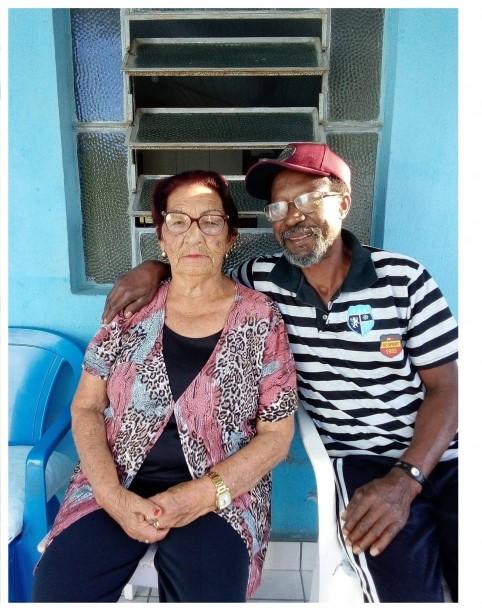 #Pracegover foto: na imagem há um homem e uma mulher, cadeiras e uma casa
