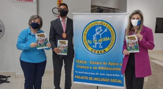 #Pracegover foto: na imagem há três pessoas e um cartaz