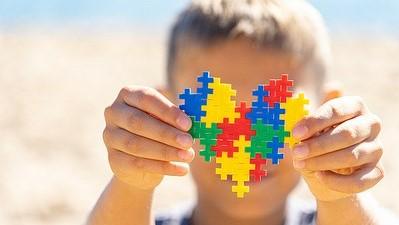 #Pracegover Na foto, criança segurando um coração feito com peças coloridas