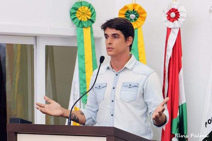#Pracegover foto: na imagem há um homem, microfone e bandeiras