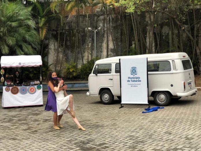 #Pracegover foto: na imagem há um veículo, duas meninas e uma mulher e uma barraquinha