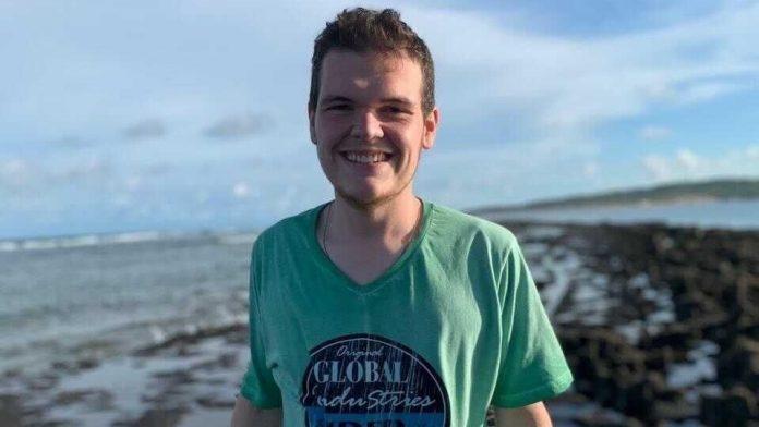 #Pracegover foto: na imagem há um jovem de camiseta verde e o mar