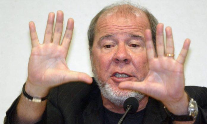 #Pracegover foto: na imagem há um homem com as mãos levantadas e um microfone