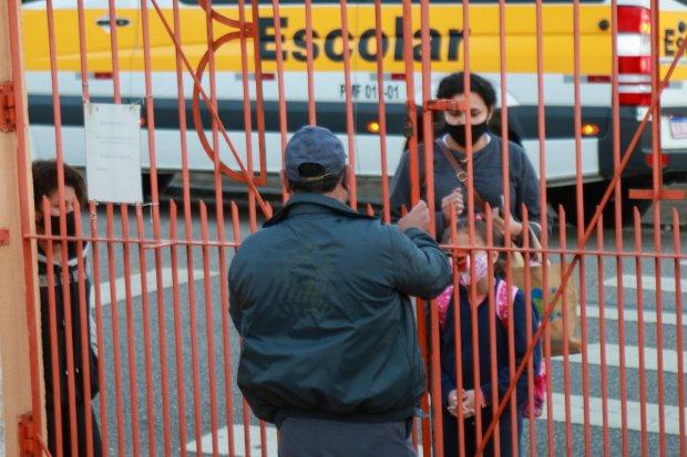#Pracegover foto: na imagem há pessoas, ônibus escolar e grades