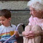 #Pracegover Na foto, criança e idosa sentados em uma escada