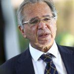 #Pracegover Foto: na imagem há um homem com o cabelo grisalho, de óculos e de terno com gravata