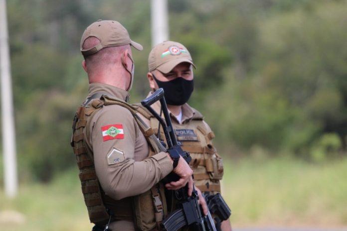 #Pracegover foto: na imagem há dois homens e uma arma