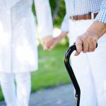#Pracegover foto: na imagem há um idoso caminhando com o auxilio de uma profissional de saúde e uma bengala