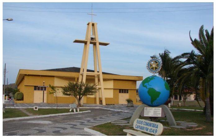 #Pracegover foto: na imagem há uma construção, cruz, árvores