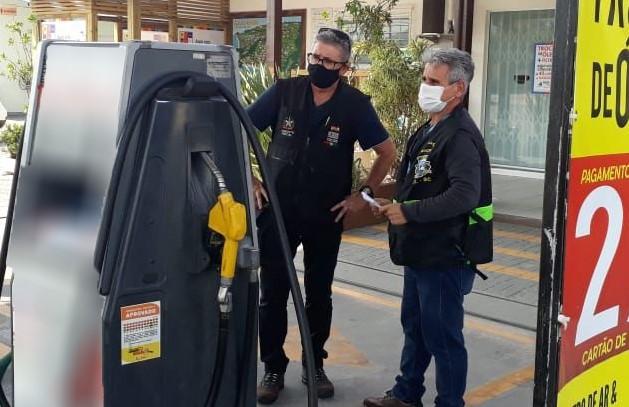 #Pracegover foto: na imagem há dois homens e uma bomba de gasolina