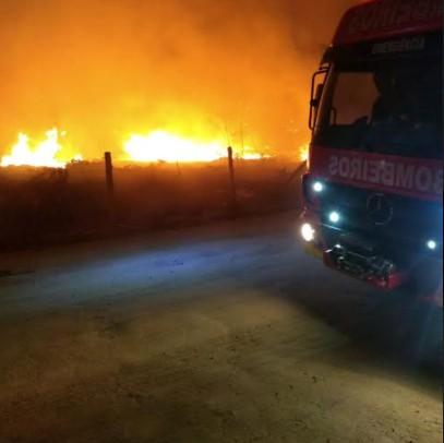 #Pracegover foto:: na imagem há um veículo do corpo de bombeiros, um terreno e fogo