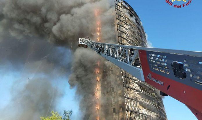 #Pracegover foto: na imagem há um prédio, fumaça e uma estrutura metálica