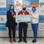 #Pracegover Foto: na imagem há três pessoas segurando um cheque simbólico
