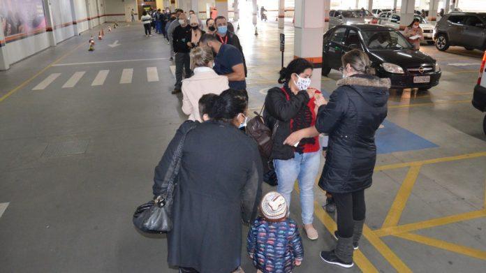 #Pracegover Na foto, pessoas em fila sendo vacinadas