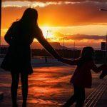 #Pracegover Na foto, mulher de mãos dadas com uma menina e ao fundo o por do sol