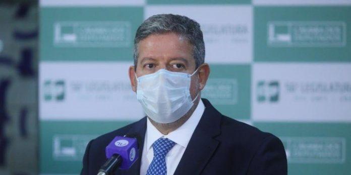 #Pracegover foto: na imagem há um homem de terno e com máscara e um microfone