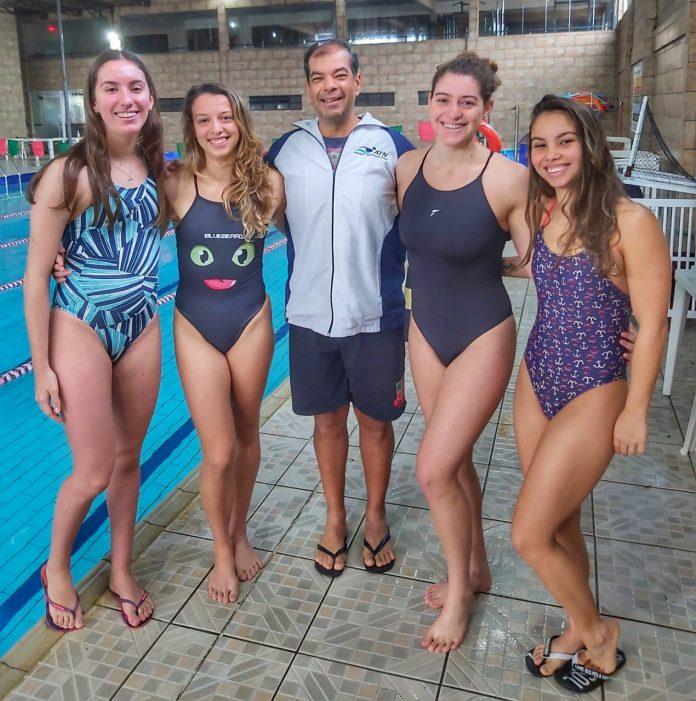 #Pracegover foto: na imagem há um homem e quatro mulheres e uma piscina