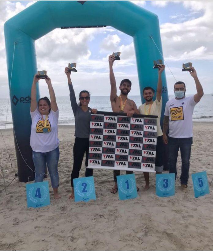 #Pracegover foto: na imagem há cinco pessoas, placas de números, o mar e areia