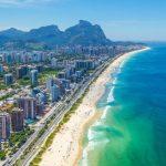 #Pracegover Na foto, prédios na beira do mar e ao fundo montanhas