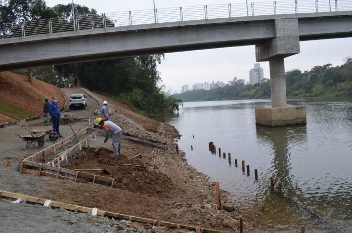 #Pracegover Foto: na imagem há um rio, uma ponte, árvores e homens