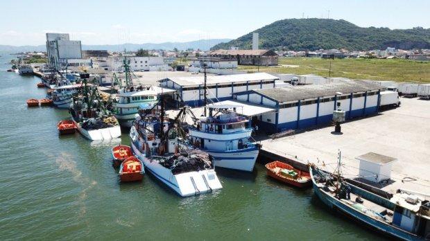 #Pracegover foto: na imagem há embarcações, construções e o mar
