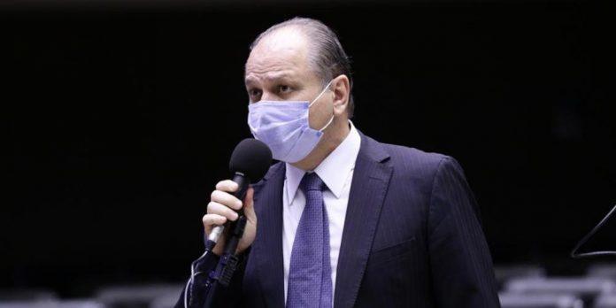 #Pracegover foto: na imagem há um homem de máscara, terno e microfone
