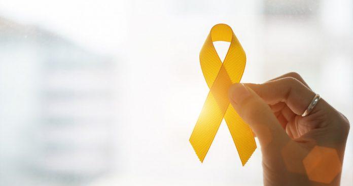 #Pracegover foto: na imagem há uma mão e um laço amarelo