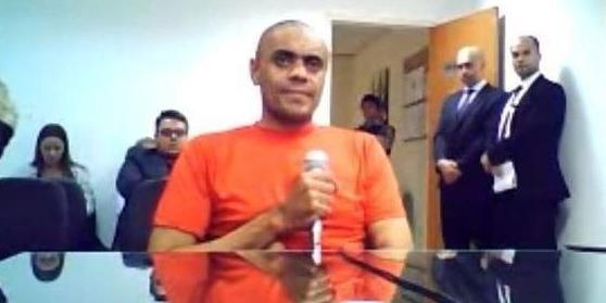 #Pracegover Na foto, Adélio está sentado atrás de uma mesa durante depoimento