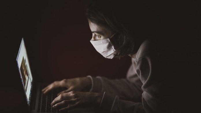#Pracegover Na foto, mulher usando máscara enquanto usa um notebook