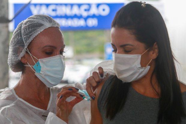 #Pracegover foto: na imagem há duas mulheres. Uma vacinando e outra sendo vacinada