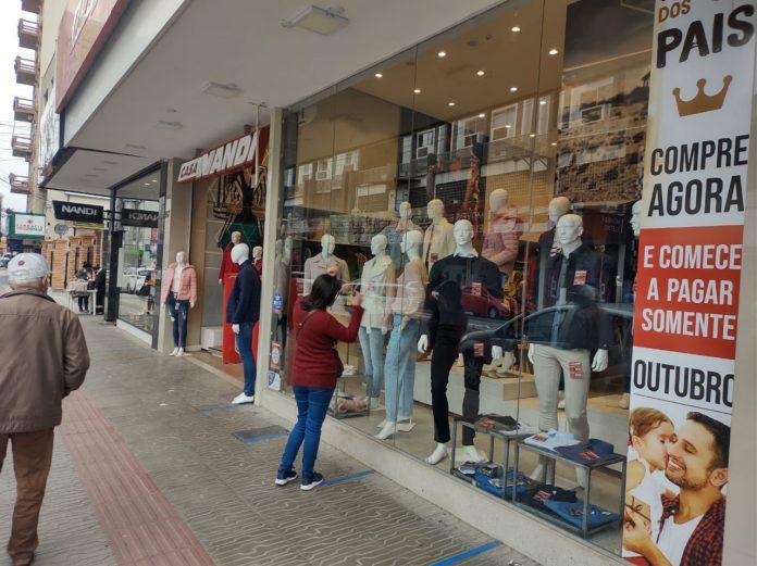#Pracegover Foto: na imagem há pessoas, e uma vitrine de loja
