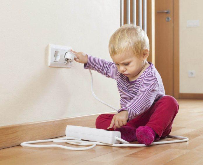 #Pracegover foto: na imagem há uma criança, porta, tomada e fio elétrico