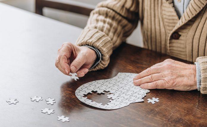 #Pracegover foto: há uma mesa, um quebra cabeças , mãos, braços e o peito de uma pessoa idosa