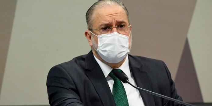 #Pracegover foto: na imagem há um homem de máscara, de terno e um microfone