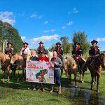 #Pracegover foto: na imagem há pessoas, equinos, árvores e um cartaz
