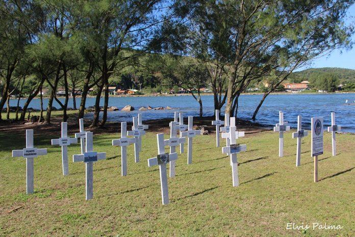 #Pracegover foto: na imagem há diversas cruzes, um lago, grama e árvores