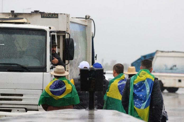 #Pracegover foto: na imagem há pessoas com a bandeira do Brasil e um caminhão