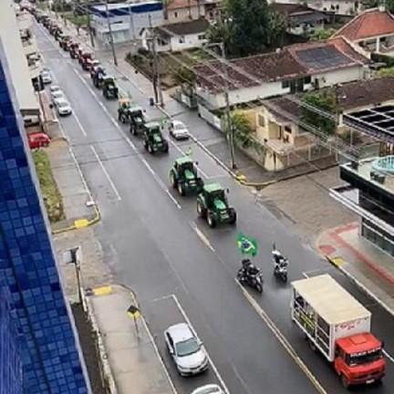 #Pracegover Na foto, veículos de passeio e agrícola e caminhões na avenida