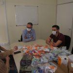 #Pracegover foto: na imagem há pessoas com máscara, mesa, cadeiras e produtos de saúde
